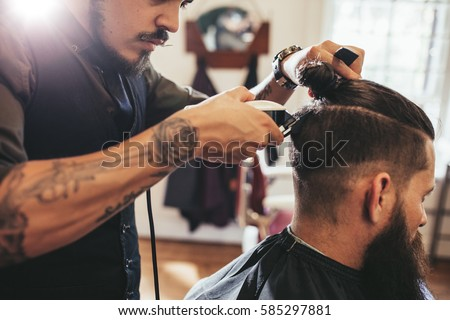 Close up shot of man getting trendy haircut at barber shop. Male hairstylist serving client, making haircut using machine and comb.