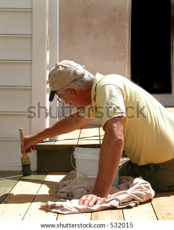 Close up shot of man on knee brushing on deck stain