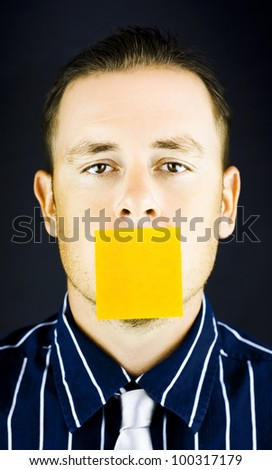 Close up shot of man with blank, yellow paper note over his mouth on black background