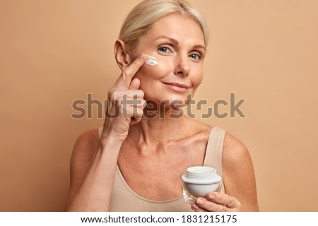 Close up shot of middle aged beautiful woman applies anti aging cream on face undergoes beauty treatments cares about skin poses against beige background. Wrinkled female model with cosmetic product