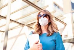 Close-up shot of middle aged businesswoman wearing protective face mask and holding notebook in her hands while walking on the street during coronavirus pandemic.