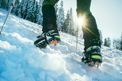 Close up shot of mountain boots with crampons and snow gaiters with backlight sun beams and snowy spruces on background . High mountaineer pounding boots in hard snow ascending UP on the summit.