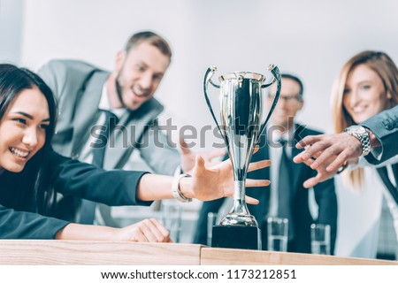 close-up shot of multiracial businesspeople trying to catch champion cup