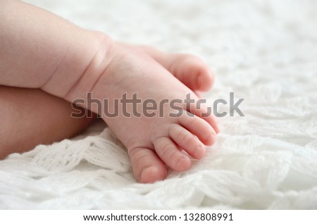 close-up shot of one month old baby's feet toes on white knitted wrap