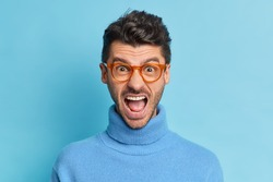 Close up shot of outraged irritated man keeps mouth widely opened screams with annoynace expresses negative emotions wears spectacles and poloneck poses against blue background. Negative emotions