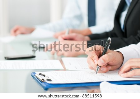 Close up shot of people compiling forms during a business conference