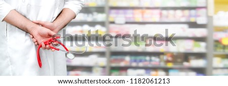 Close-up shot of pharmacist hands holding medical equipment. The pharmacist is working in a pharmacy.