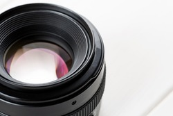 Close-up shot of photo lens on a white wooden table.
