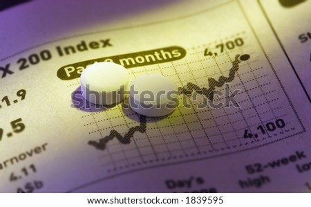 Close-up shot of pills on stock price chart.