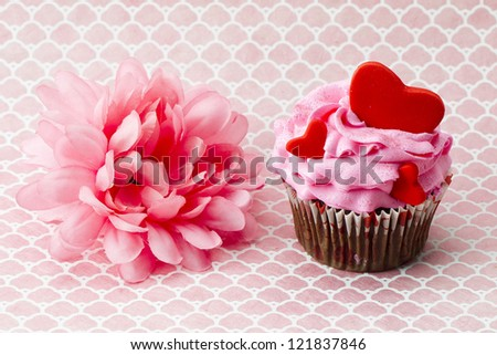 Close-up shot of pink flower and strawberry cupcake with heart shape over pink background.