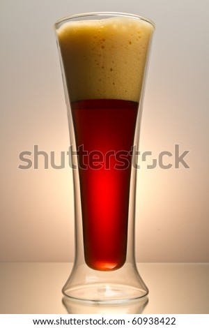 Close up shot of pint of dark beer shot on rich brown background with space for copy