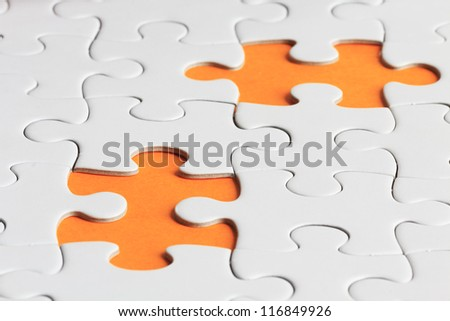 close up shot of plain puzzle with two missing pieces
