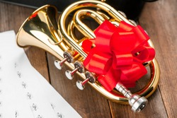 Close-up shot of pocket trumpet with red bow on wooden background. Music score sheets. Perfect gift for trumpet player.