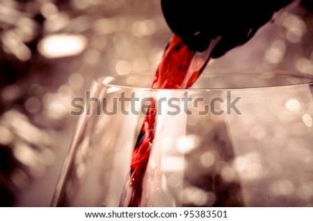 Close-up shot of pouring red wine into glass