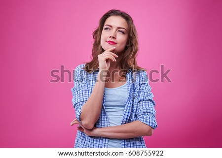 Close-up shot of pretty girl thinking about the plans isolated over pink background. Woman in checked shirt standing in the studio and looking upwards