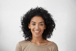 Close up shot of pretty girl with perfect teeth and dark clean skin having rest indoors, smiling happily after received good positive news. Beautiful young woman with Afro hairstyle relaxing at home