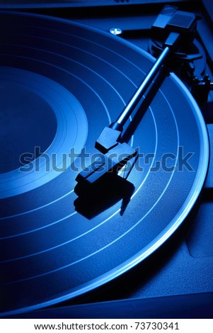 Close up shot of record player with moody blue lighting