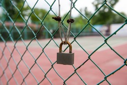Close up shot of rusty padlock on green wired fence. tennis court in the background,