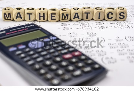 Close up shot of scientific calculator and mathematical equations sheets. Wooden letter blocks assemble the word mathematics.