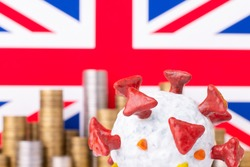 Close up shot of self made coronavirus cell with britain flag and stacks of coins in a background. Concept of coronavirus and economy in Great Britain.
