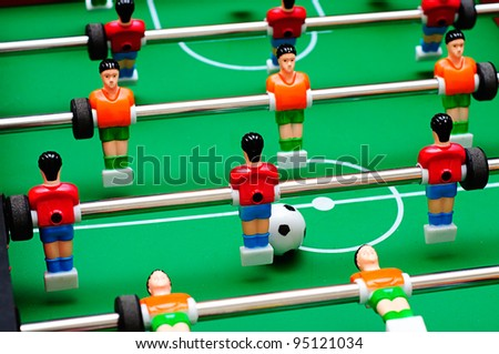 close up shot of soccer table game with green field and red and yellow plastic football players