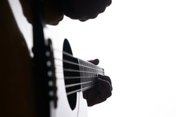 Close up shot of strings and guitarist hands playing acoustic guitar over white