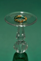 Close up shot of stylish handmade ring made of epoxy resin with golden foil inside on wine glass isolated over green background. Jewelry fashion photography, making jewelry concept