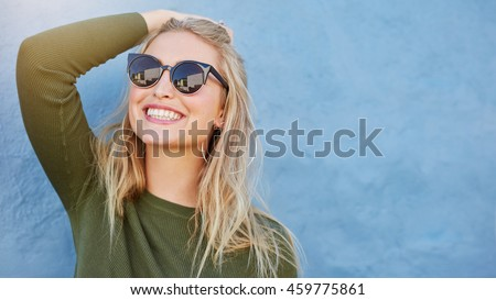 Photo of Close up shot of stylish young woman in sunglasses smiling against blue background. Beautiful female model with copy space.