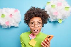 Close up shot of surprised curly woman stares surprisingly at camera holds mobile phone checks email box surrounded with memo notes makes list to do tries to be more productive poses indoor.