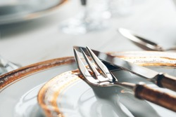 Close up shot of table setting for fine dining with cutlery and glassware