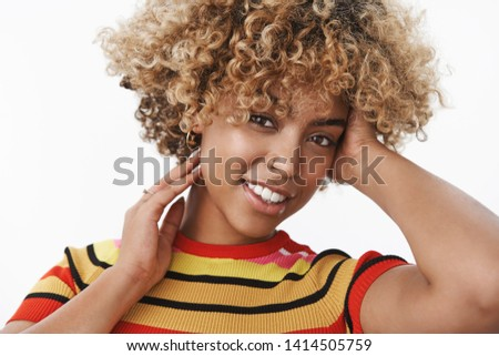 Close-up shot of tender and sensual attractive gentle african american stylish woman with fair afro haircut and pierced nose tilting head flirty and gently touching hair smiling at camera #1414505759