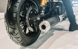Close up shot of the exhaust of a black motorcycle in the back view.