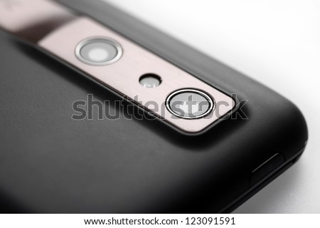 Close-up shot of the photo camera on the back of a mobile phone.