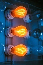 Close up shot of three incandescent bulbs lit on the panel