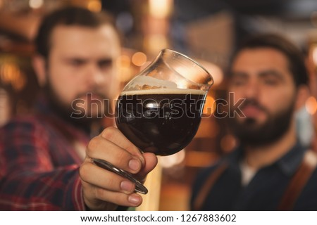 Close up shot of two brewers examining delicious dark beer in a glass, working at the beer production factory. Selective focus on a beer mug in the hands of beermakers. Quality, expertise concept #1267883602