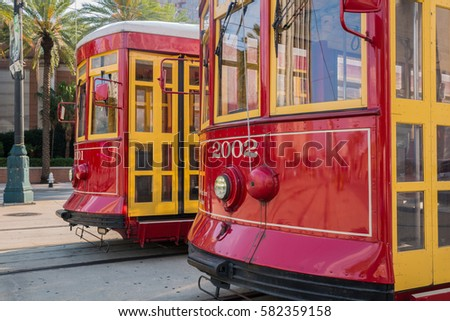 Close-up shot of two brightly colored red and yellow streetcars parked on Canal Street in New Orleans, Louisiana