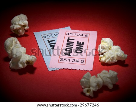 Close up shot of two generic admission tickets and some popcorns arround.