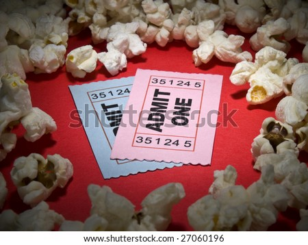 Close up shot of two generic admission tickets surrounded by popcorns.