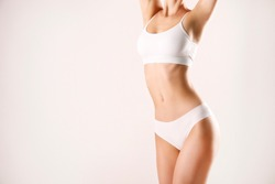 Close up shot of unrecognizable fit woman in lingerie isolated on white background. Torso of slim attractive female with flat belly in white underwear. Copy space for text.