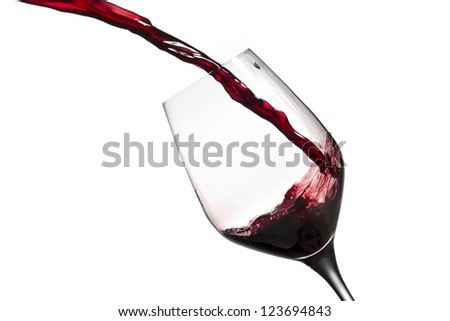 Close-up shot of wine being poured in wine glass against white background.