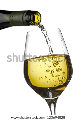 Close-up shot of wine bottle pouring wine in wine glass against white background.