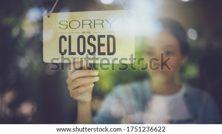 Close up shot of woman hand turning close sign board on glass door in coffee shop and restaurant during coronavirus lockdown quarantine.Business crisis concept. Stock photo ©
