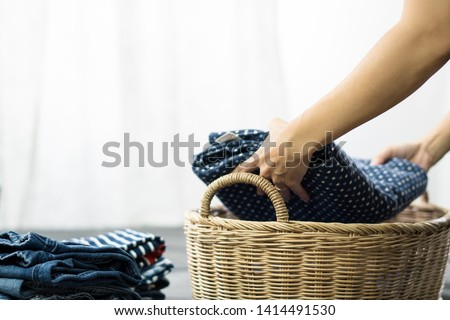 Close up shot of woman's hands doing the laundry work. She putting clean folded cloths and towels into a laundry basket. Woman, Wife, Mom daily routine housework concept. #1414491530