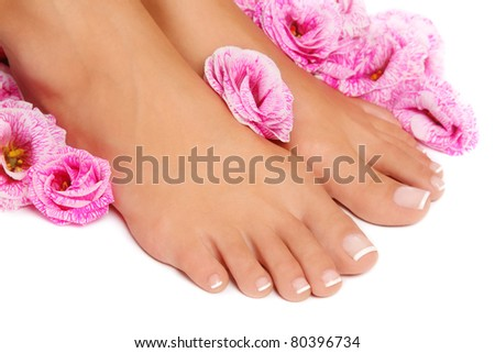 Close-up shot of woman tanned feet with french pedicure and pink flowers around on white background, selective focus