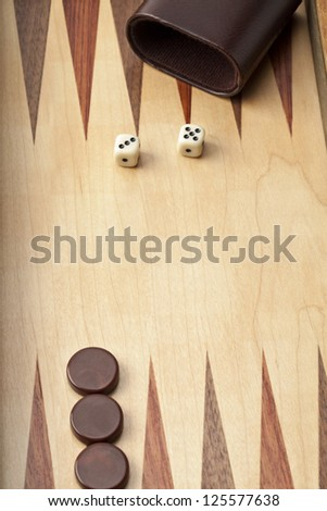 Close-up shot of wooden backgammon board with dices and brown pieces with cup.