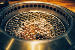 Close up shot of Yakiniku Japanese grilled meat on wire mesh or gridiron over wood charcoals.