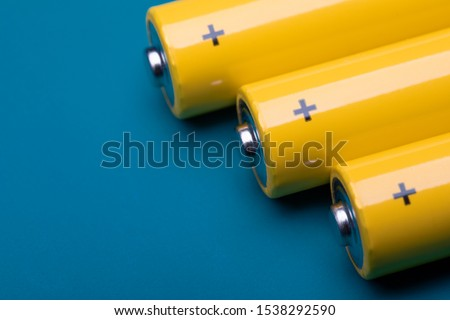 Close up shot of yellow AA alkaline or rechargeable NiMH batteries on blue background, shallow focus #1538292590