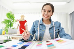Close up shot of young beautiful Asian  female fashion designer smiling and choosing the fabric sample from a catalog. She is proud  and ready for her newest collection.