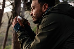 Close up shot of young man drinking hot coffee, taking break during hiking. Male hiker taking rest outdoors.