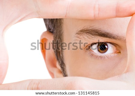 Close-up shot of young man's eye looking through frame - stock photo